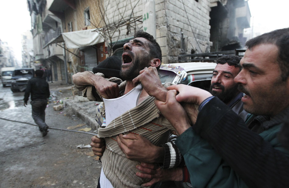 A father reacts after the death of two of his children, whom activists said were killed by shelling by forces loyal to Syria's President Bashar al-Assad, at al-Ansari area in Aleppo